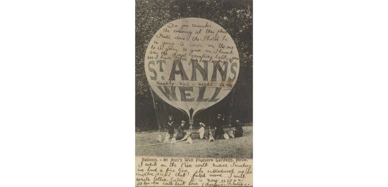 A postcard from c.1905 of a hot air balloon in St Ann's Well Gardens, Brighton, England. The handwritten message reads: 'Do you remember the evening at this place. Fred's done the photo's he is going to write on the one he is going to give me, I havent seen the sweet creature lately, you see I have other fishes to fry. Nearly mid-night ta ta. I went on the Pier with nurse Sunday we had a fine time, she introduced me to another Frank that fated name.. I will write letter later it is now 11.15 pm so bye -bye with best love (darling) Beatie x x '