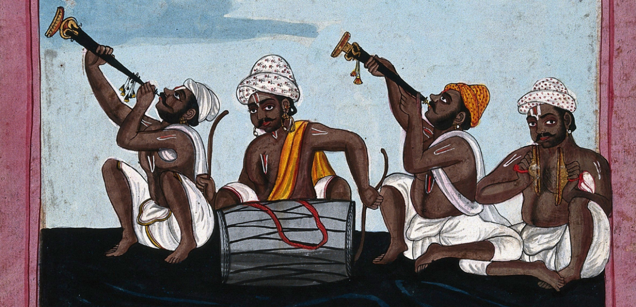 Four seated Indian musicians play instruments